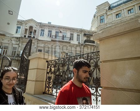 Baku, Azerbaijan - May 2, 2019: Male Female Students Walking Near Baku School On A Sunny Day