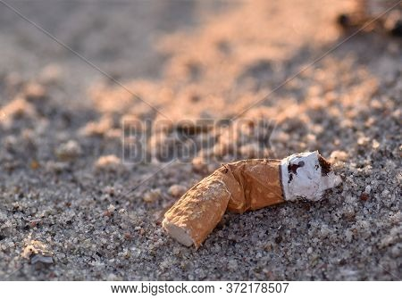 Closeup Of An Old And Weathered Cigarette Butt Abandoned On The Beach. The Cigarette Butt Is Laying