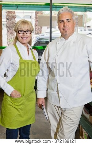Portrait of a senior woman with mid adult chef in market