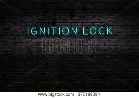 Neon Sign With Inscription Ignition Lock Against Brick Wall. Night View