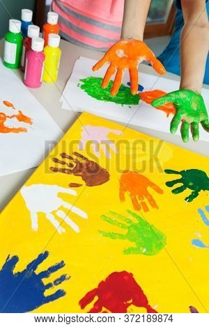 Close-up of paint covered hands and colorful handprints on papers