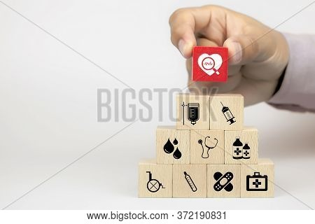 Hand Picking Health Icon On Cube Wooden Toy Blocks Stack In Pyramid With Other Medical Icons. Concep