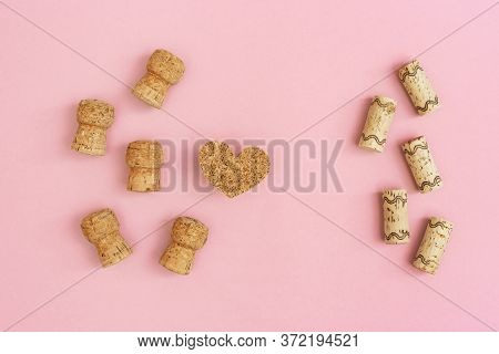 Corks From Champagne And Wine Heart From Cork Material On Pink Colored Paper With Copy Space. Celebr