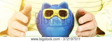 Aged Person In Yellow Pullover Holds Hands At Blue Money Box Of Pig With Sunglasses Form Under Brigh