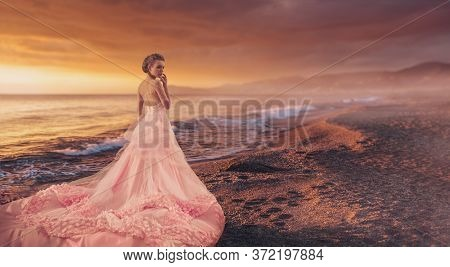 Wedding fashion. Full length portrait of a beautiful bride girl in a luxuriant pale pink dress standing on on the ocean in the sunset.