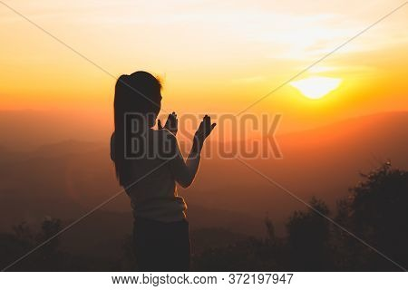 A Women Is Praying To God On The Mountain. Praying Hands With Faith In Religion And Belief In God On