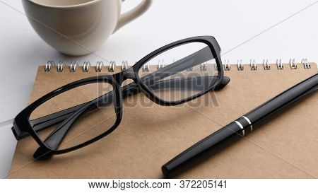 Close-up Of Pen And Glasses On A Notebook