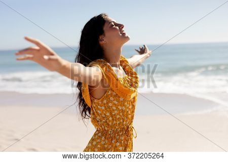 A Caucasian woman with long dark hair wearing a yellow sundress, on holiday, enjoying free time, on an idyllic sunny beach with eyes closed and arms outstretched, blue sky and sea in the background