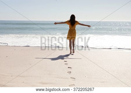 Rear view of Caucasian woman with long dark hair wearing a yellow sundress, walking barefoot on an idyllic sunny beach with her arms in the air, with blue sky and sea in the background
