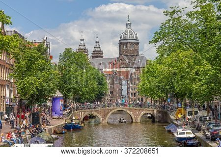 Amsterdam, Netherlands - 31 May, 2014: Tourists Walking By A Canal In Amsterdam. Amsterdam Is The Ca
