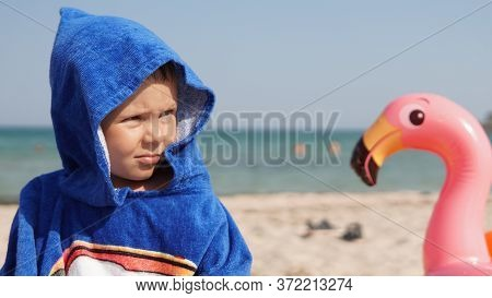 Close-up Portrait Of Glad Child In Blue Hood Of Bathrobe Standing With Toy Pink Flamingo On Sea Beac
