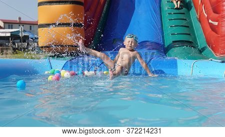 Child Slide Down From Inflatable Water Slide. Aqua Amusement Park Of Sea Resort. Family Vacation And
