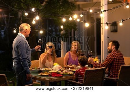 Side view of a senior Caucasian man standing and making a toast holding a glass of red wine during a multi-generation family celebration meal outside, his family is sitting at the dinner table