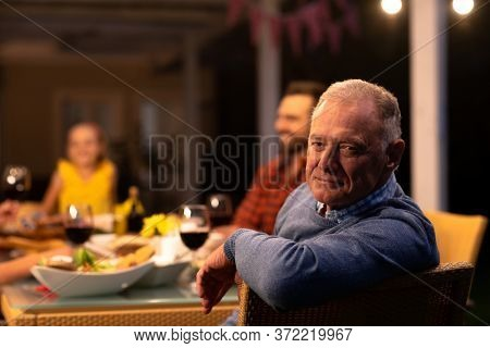 Portrait of a senior Caucasian man sitting at the table and turning to camera smiling during a multi-generation family celebration meal outside, with members of the family sitting at the dinner table