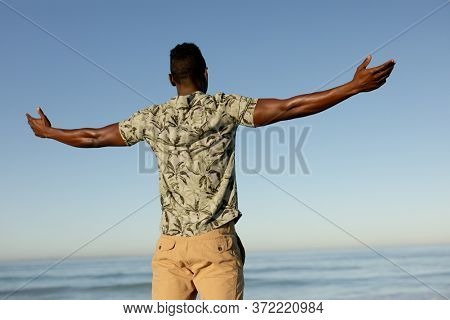Rear view of a happy, attractive African American man enjoying free time on beach, wearing a Hawaiian shirt, sun shining on his face with his arms outstretched. Relaxing summer vacation.