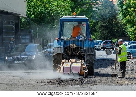 Uzhgorod, Western Ukraine - June 11, 2020: Employees Of Municipal Services, Repair Pavement In The C