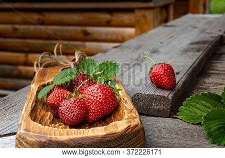 Few Bright Red Organic Strawberries On Handmade Wooden Board And On Old Textured Wooden Surface. Unf