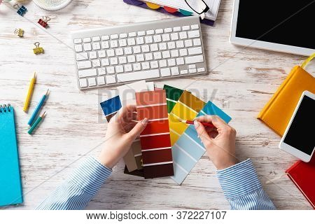 Interior Designer Choosing Colors From Swatches At Wooden Desk. Office Workplace With Computer Keybo
