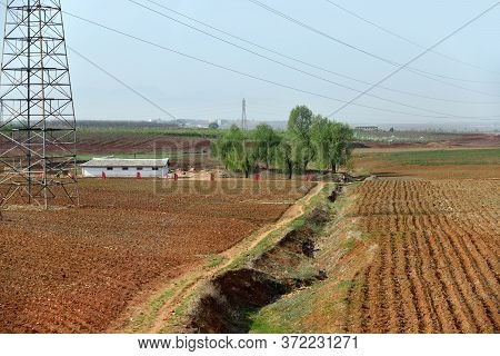 Countryside Landscape, North Korea. Cultivated Agricultural Fields And Electric Power Line Mast