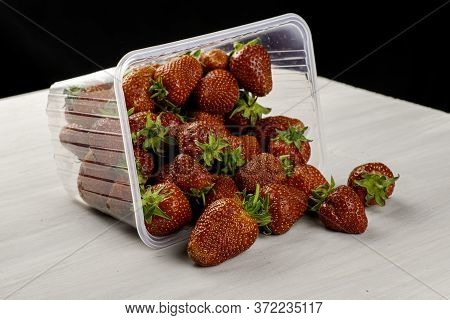 Overturned Transparent Plastic Container With Red Ripe Juicy Strawberries Scattered On A Table