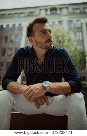 Young Man Sits And Ponders On Bench Against Background Of Modern Building. Closeup.