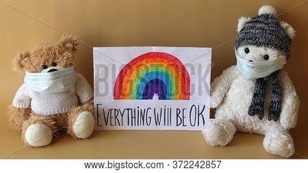 Soft Toys Bears In Protective Face Masks Next To A Sheet Of Paper With Rainbow And Phrase