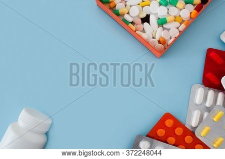 Colorful Tablets And Capsules In An Orange Box, Bottle, Container, Tablets In A Package, Are Located