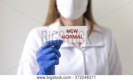 New Normal Text Inscription On Paper Card In Hands In Protective Gloves Of Blurred Doctor. New Norma