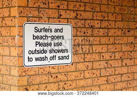 Notice On A Brick Wall - Surfers And Beach-goers Please Use Outside Showers To Wash Off Sand.