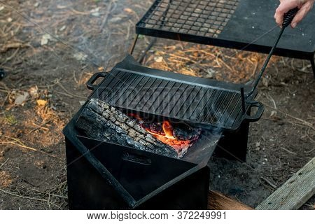 Setting The Campfire In A Portable Foladble Firepit For A Camp Cooking On Cast Iron Plate.