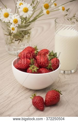 White Bowl With Strawberries And A Glass Of Milk With A Bouquet Of Daisies