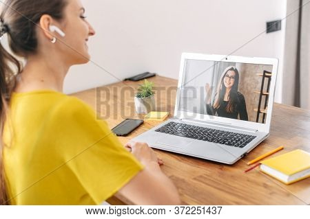 A Young Woman Sits Indoor And Using App On Laptop For Video Call To Female Coworker, Colleague Or Fr