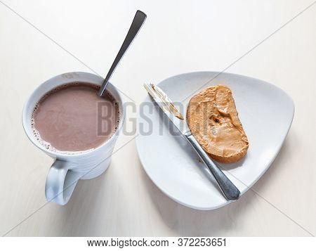 Top View Of Cup With Cocoa And Toast With Peanut Butter On Plate On Table