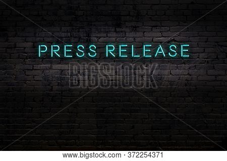 Neon Sign On Brick Wall At Night. Inscription Press Release
