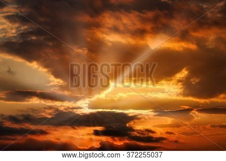 Orange Sunset With Sun Rays In The Clouds.
