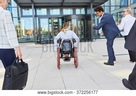 Woman in a wheelchair together with business colleagues before a congress or event