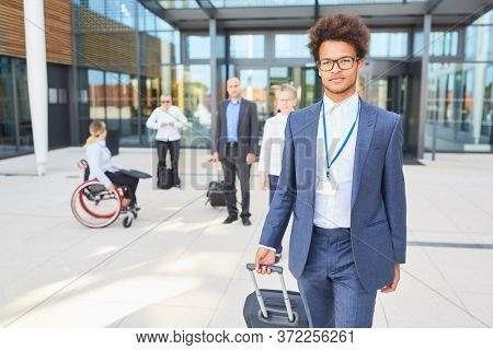 African businessman with trolley on departure from meeting or congress