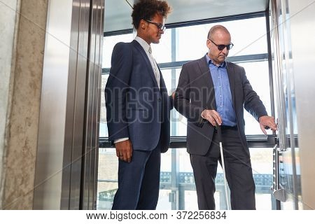 Blind man with a cane and young African businessman in the elevator