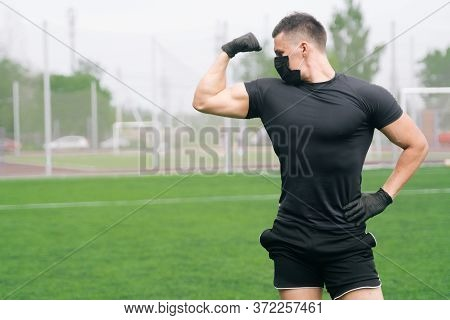 A Portrait Of A Sportsman In Medical Mask Shows The Muscles Of The Bicep. Fitness Trainer Boasts Of
