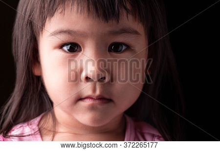 Portrait Face Of Asian Little Child Girl With Confidence Expression On Dark Background.