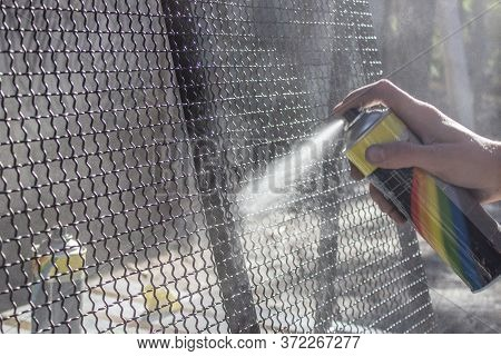 Spray Can With Paint In Hand. Black Paint Is Sprayed From The Spray Can On The Metal Net. Workman Wo