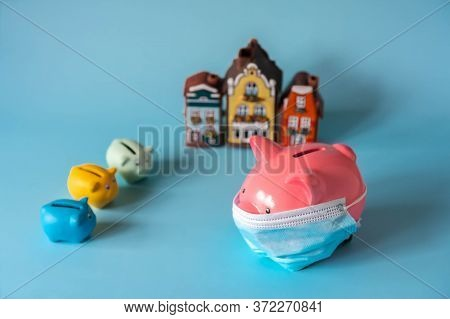 Piggy Bank With Medical Mask, Savings For Real Estate. Piggy Bank, Small Piggy Banks And House Model