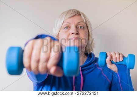 Portrait Of Elderly Woman In Blue With Dumbbells. Active Senior Woman Lifting Dumbbells. Closeup Of