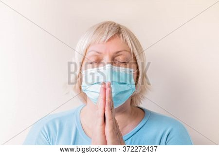Senior Woman With Facial Mask Praying. Portrait Of Elderly Woman In A Medical Mask Praying. Mature F