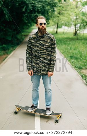 Stylish Man Ride On Skateboard In White Shirt On City Street. Portrait Of Handsome Bearded Hipster M