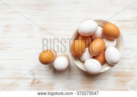 Plate With Brown And White Chicken Eggs And Boiled Eggs In Holders On Wood Table. Brown And White Eg