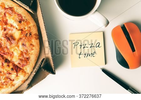 Pizza In Box, Cup Of Coffee, Laptop, Computer Mouse, Pen And Sticker With Text Pizza Time On Desk In