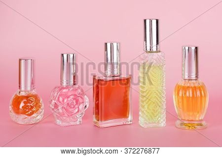 Different Colorful Transparent Perfume Bottles On Pink Background. Aromatic Essence Bottles. Perfume