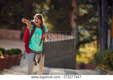 young female delighted by sightseeing in italy, showing thrilled with index finger what she saw