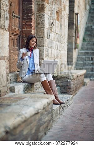 beautiful young caucasian female sitting on stairways drinking coffee outdoor, looking at laptop